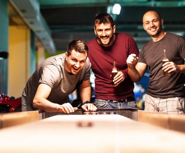 Shuffleboard turnering til fredagsbar og firmafester. 3 kollegaer hygger med mega shuffleboard